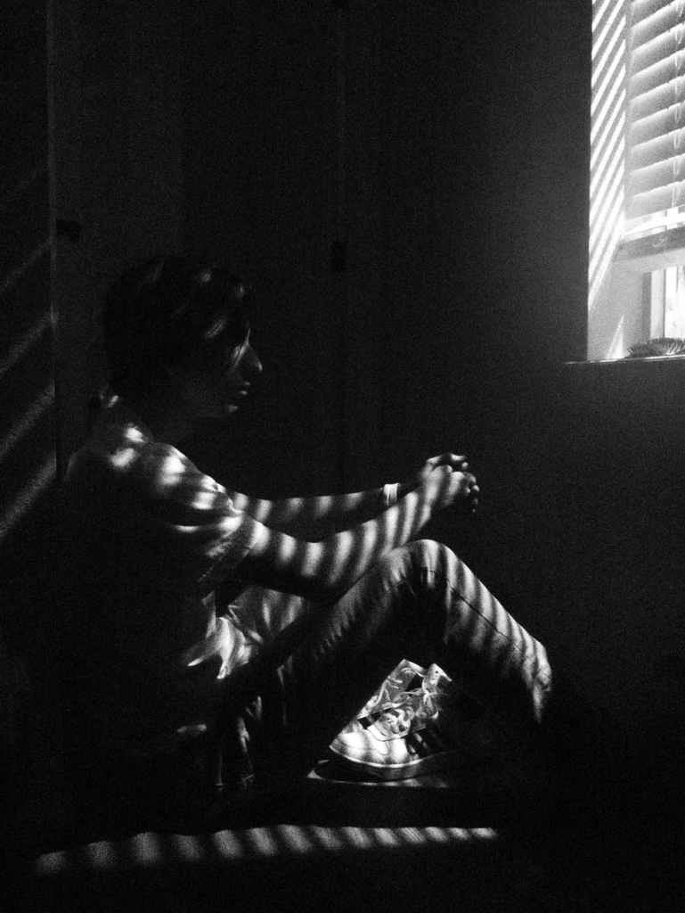 Person sat on floor in darkness with lines of light coming through the window blinds