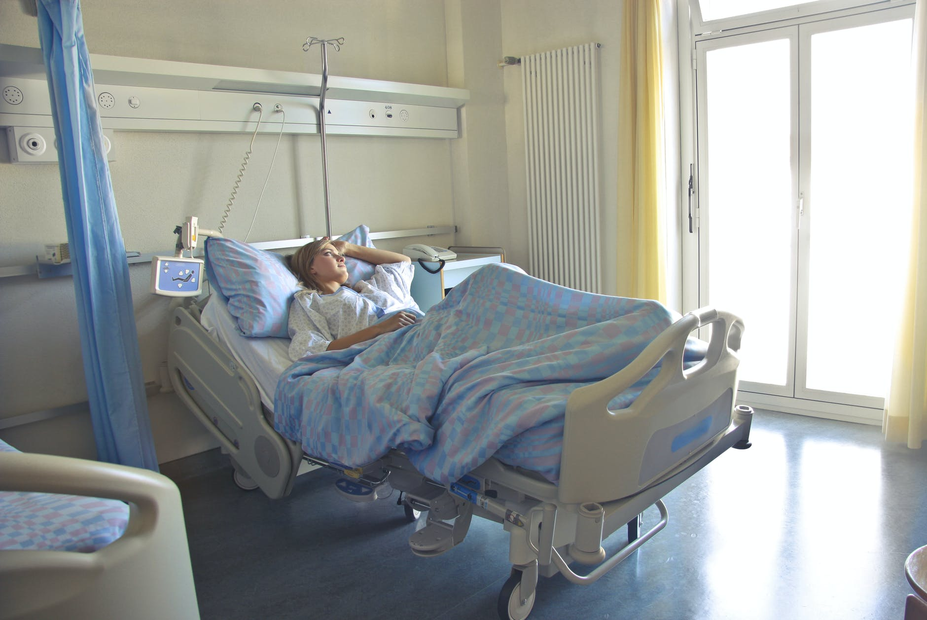 photo of woman lying in hospital bed