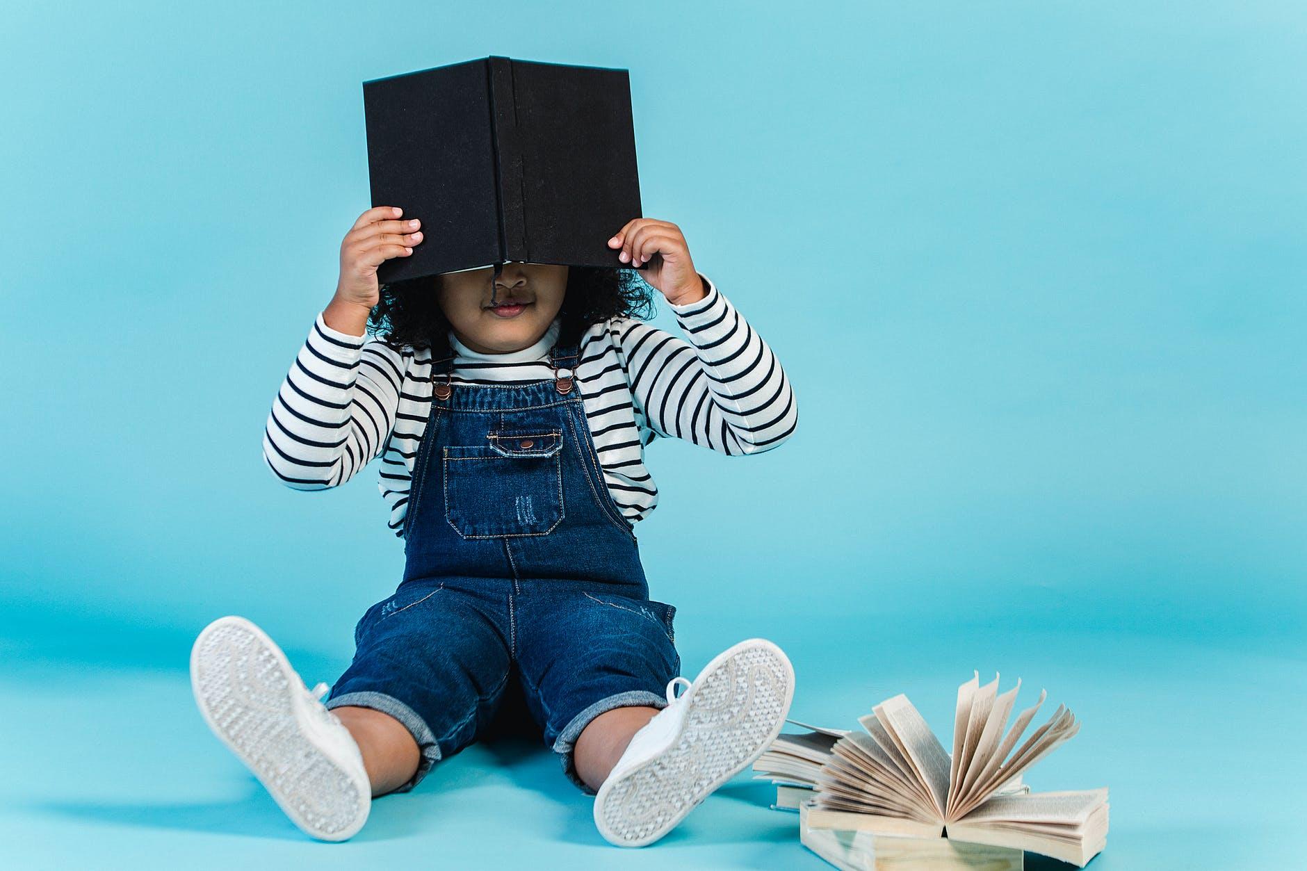 Child hiding in a book.